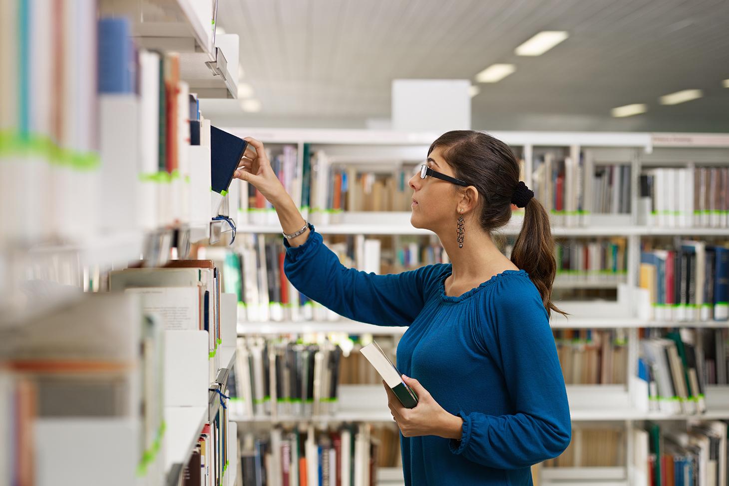 Une étudiante consulte des ouvrages