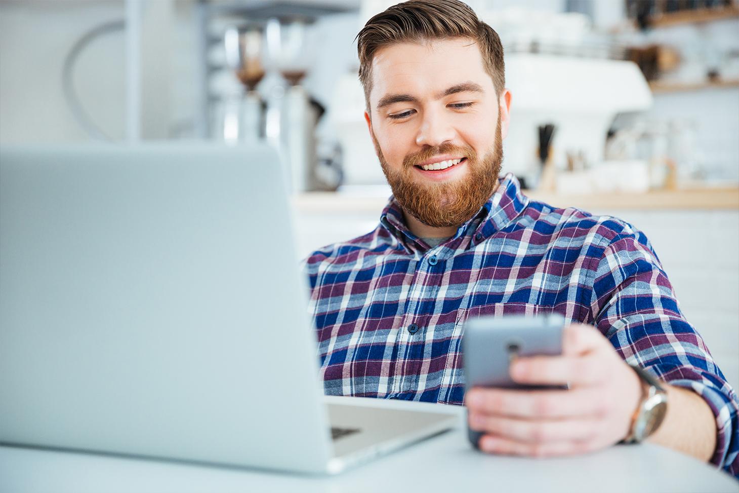 Un étudiant consulte son emploi du temps depuis son smartphone et son ordinateur portable