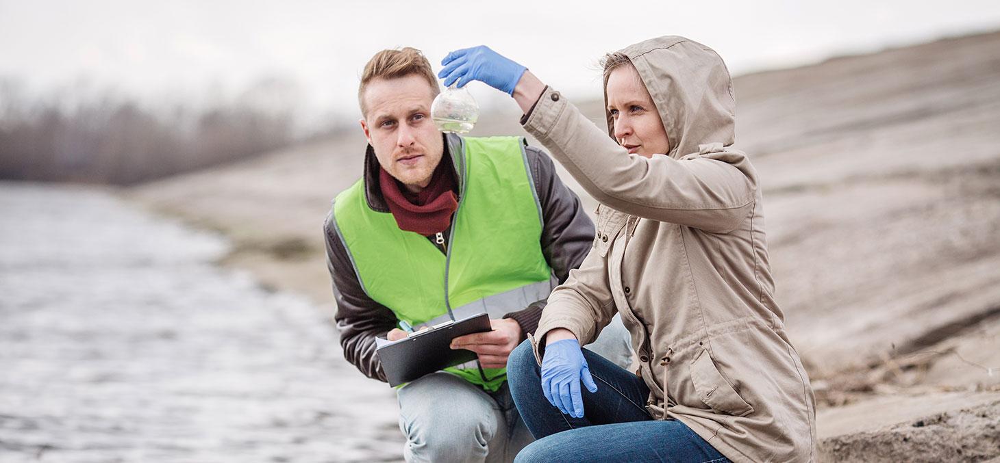 Deux chercheurs effectuent un prélèvement d'eau dans un cours d'eau